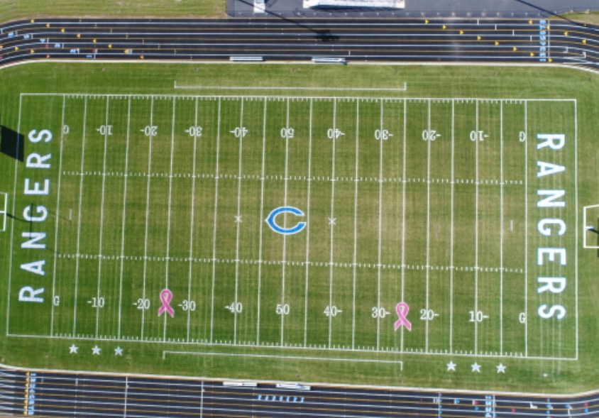 Pink Breast Cancer Ribbon Stencils Painted on Football Field